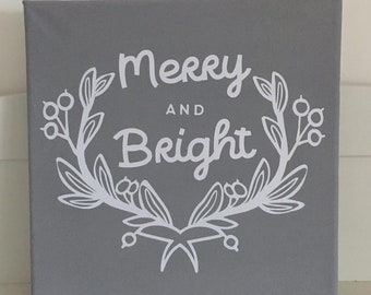 Grey painted 20cm stretched canvas with white Merry and Bright with wreath of leaves and berries