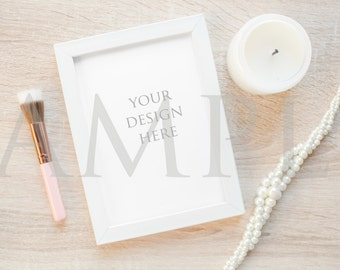 Download Free White frame mockup with candle, pearls, and pink makeup brush on wood stock photo PSD Template
