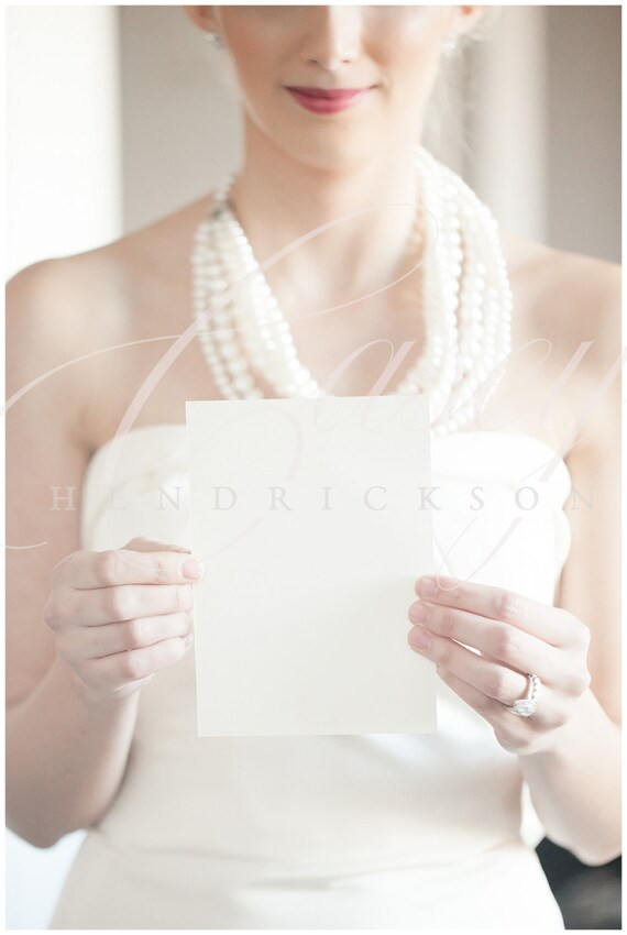 Image of bride holding 5x7 blank invitation stationery card