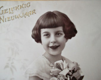 shiny postcard of a pretty little girl with flowers, vintage postcard