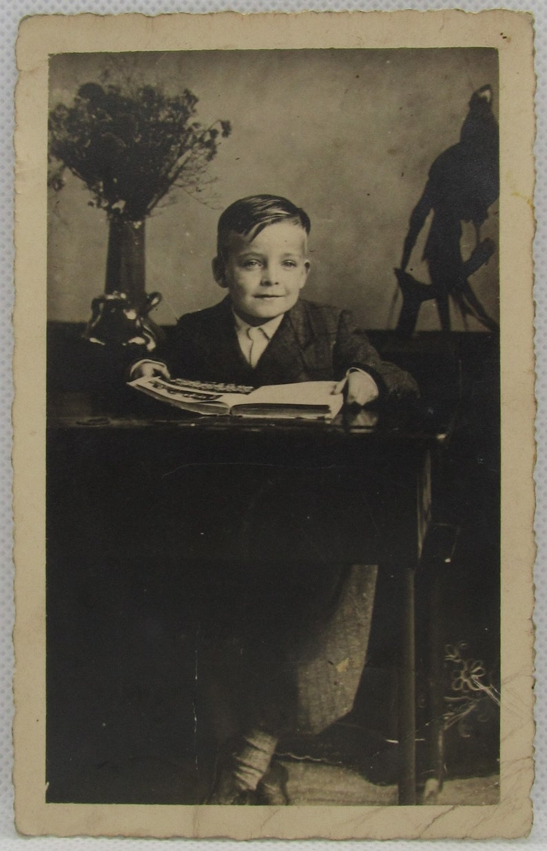 old photo postcard Vintage photo postcard of a cute boy sitting at an antique desk with a book