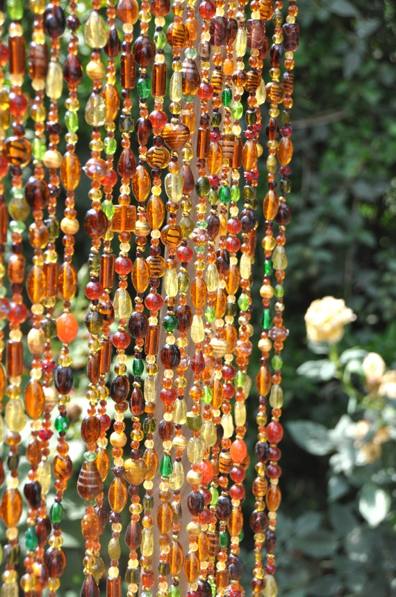 Beaded Curtain In Shadows of Brown Amber and Gold with touches of green-a brass bell on the bottom of each beaded strand (made to order)