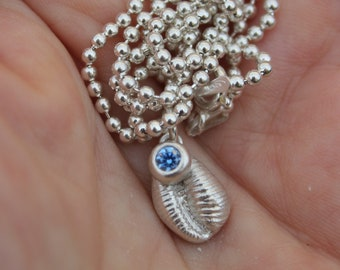 Silver cowrie shell pendant inspired by the seashore with a sea coloured swarovski crystal gem