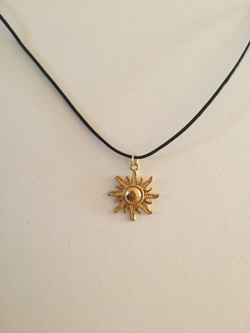 Gold Sun on black leather cord