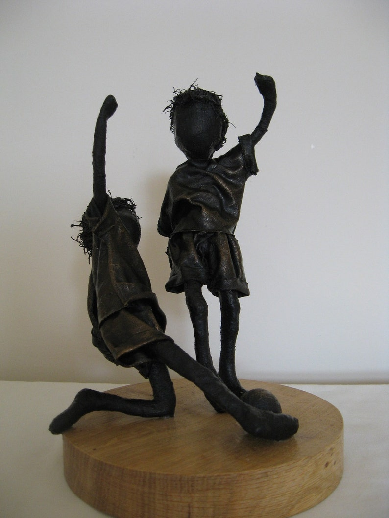Little Footballers.  Sculpture of boys playing football. image 0
