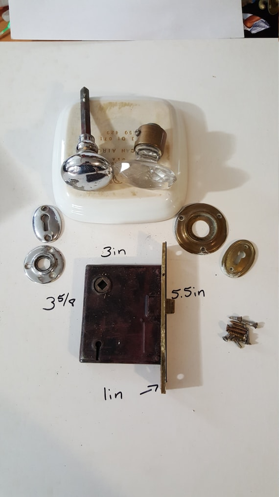 Salvaged crystal and chrome doorknobs with mortise and key hole covers.