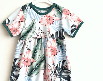 Girls dress with short sleeves. Light blue jersey fabric with tropical leaves and flowers