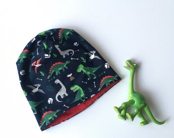 Beanie hat, slouchy hat. Kids to adult sizes. Dark blue with dinosaurs. Red reverse side. Reversible beanie hat
