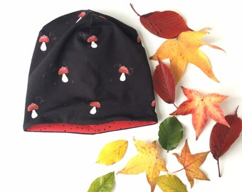 Beanie hat, slouchy hat. Kids to adult sizes. Dark brown with toadstools. Red reverse side. Reversible beanie hat