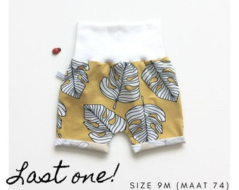Yellow baby shorts with monstera leaves.  Organic cotton knit fabric. Size 9 m.
