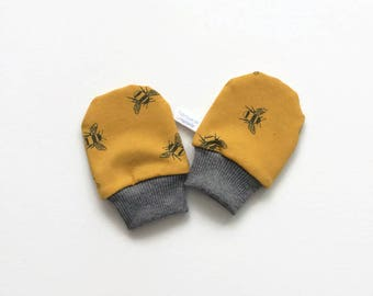 Yellow baby mittens with bees