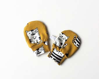 Yellow baby mittens with cats