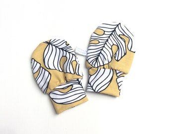 Yellow baby mittens with leaves