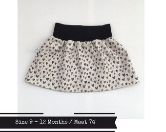 Last one: Beige baby or toddler skirt with hearts. Black waist band. Size 9 - 12 months