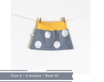Grey skirt with white dots.  Yellow waist band. Size 3 - 6 months