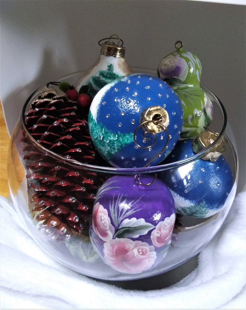 """Glass bowl full of hand decorated ornaments and """"Fir Cones"""" that have been dried and dyed with a red stain.  Very pretty."""