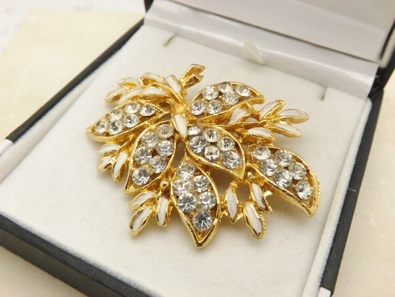 A superb large classic flower and leaf design vintage jewelry brooch in goldtone openwork metal and enamel with sparkly light grey stones