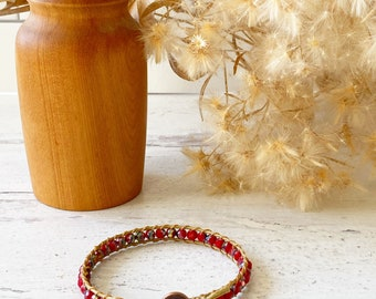 Red metallic beaded bracelet with button clasp.