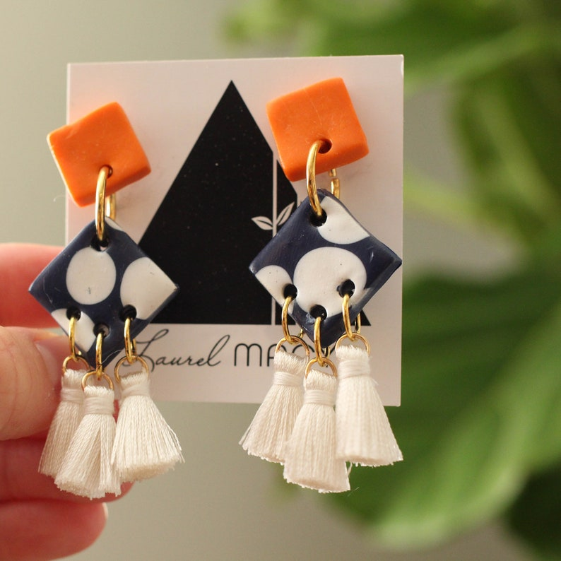 Orange with Navy Polkadot square studs with white tassels. One image 0