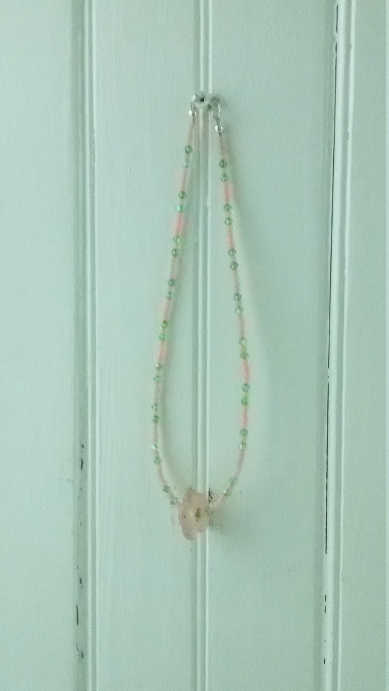 A pale pink quartz flower serves as the pendant. Light pink seed beads with green crystals Sweet pink and green choker