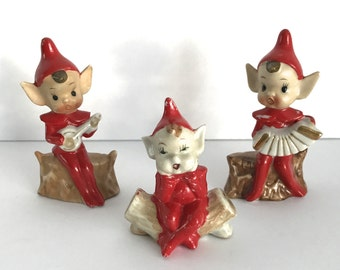 1950s Porcelain Elf Figurines. Set of 3 Elves Wearing Red Hats. Playing Instruments, Banjo and Accordion. Sitting on a Wooden Log.