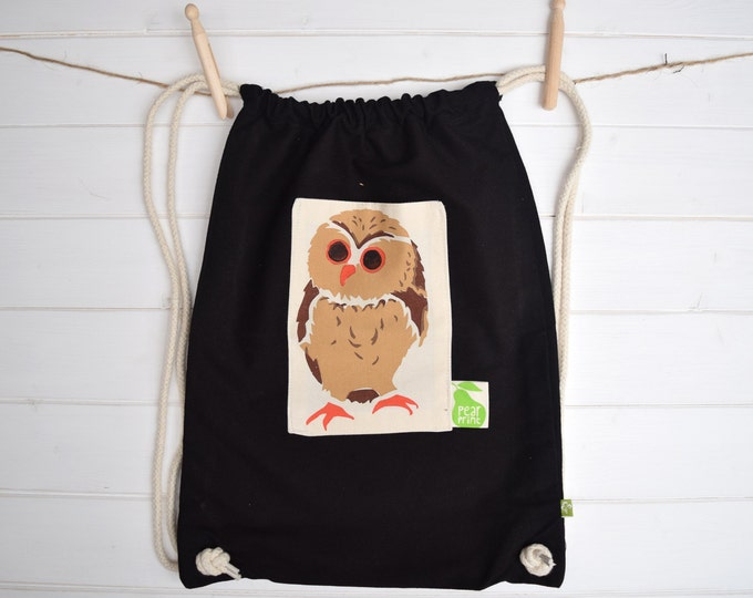 Black canvas gymbag with owl print pocket.