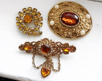 Lot of 3 topaz crystal brooches.