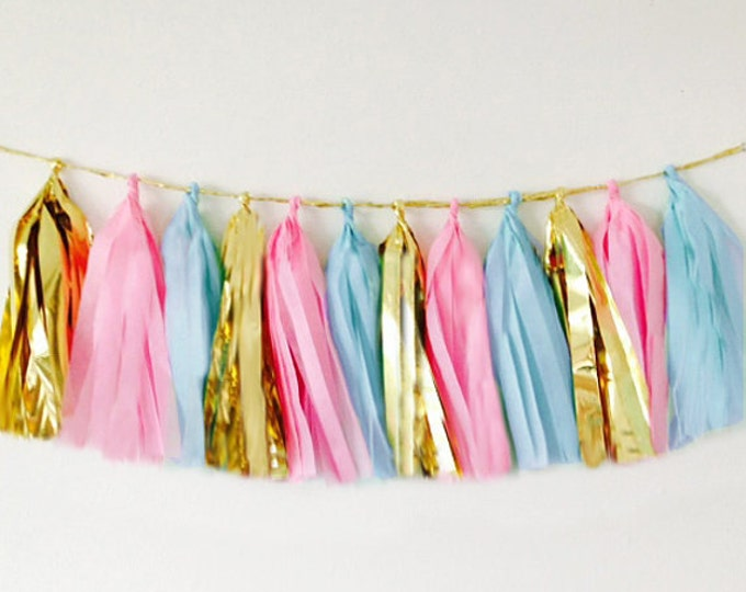 Tassel garland in light blue, light pink, and metallic gold for your gender reveal party decor, birthday party decor or baby shower decor