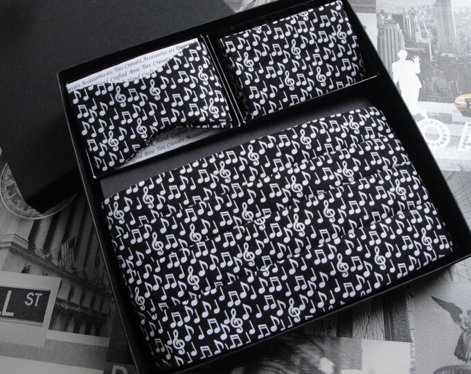 Cummerbund, bow tie and pocket square set, white notes on a black background