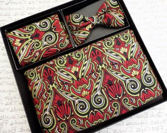 Cummerbund, bow tie and pocket square set in red, green and gold print on a black background