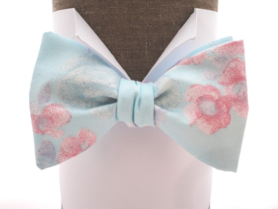 "Self tie or pre tied bow tie in pale aqua blue with pink roses, also available in pre tied, will fit up to 20"" (50cms) neck size."