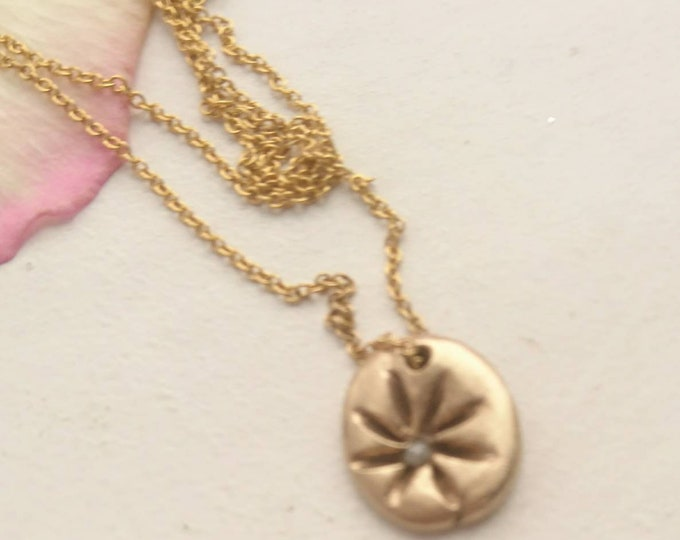 Wildflower pendant, bronze flower charm with a raw faceted white solitaire diamond