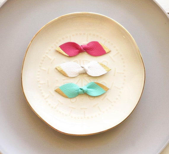 Knot leather bow clips in hot pink, white and mint with hand painted gold tip.