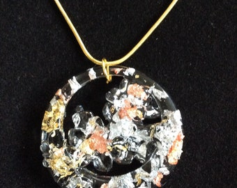 Round worked pendant in synthetic resin with gold, silver and copper leaf