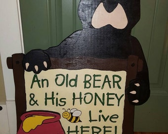 An old bear holding a sign