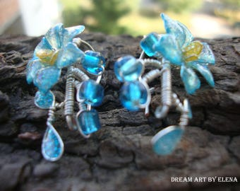 Miniature flower earrings in sparkling translucent blue, darker on the edges, with yellow stamens, stylized leaves and beads