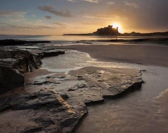 The sun rises behind Bamburgh Castle, Northumberland, UK