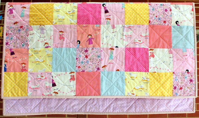 Hello Petal Modern cot quilt with a retro feel.