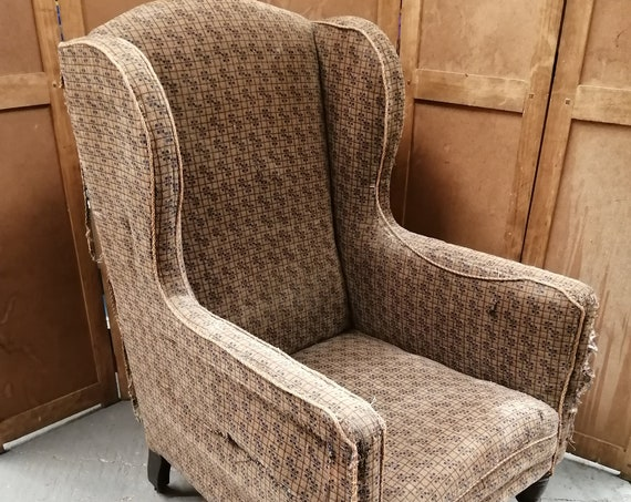Antique hump back wing armchair suitable for a reupholstery project