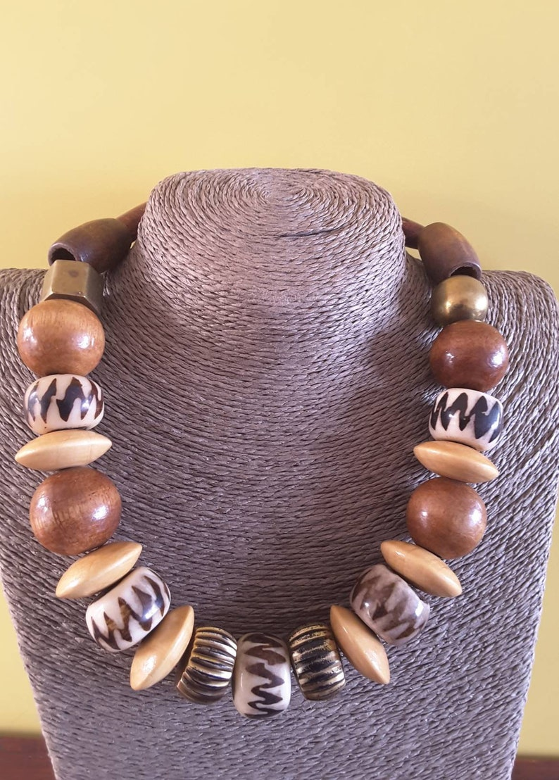 Wooden beaded necklace with gold colored beads in natural shades.