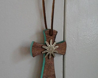 Small stained cross with teal edging and a rhinestone spur rowel.