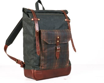 Dark creen tartan waxed canvas roll top backpack.