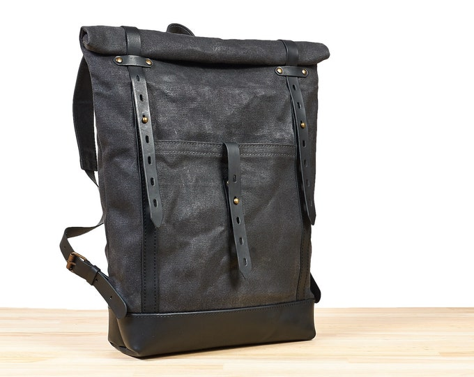 Slim waxed canvas backpack. Dark grey canvas, black leather rucksack.