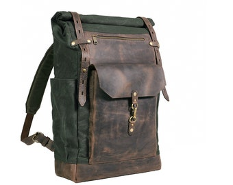 Waxed cotton roll-top rucksack. Hipster backpack in deep green color.
