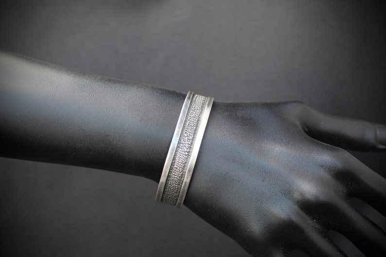 Rustic Silver Styling 3153 Sterling Silver Cuff with a Textured Center on a Black Background With a Smooth Silver Border in  Southwestern