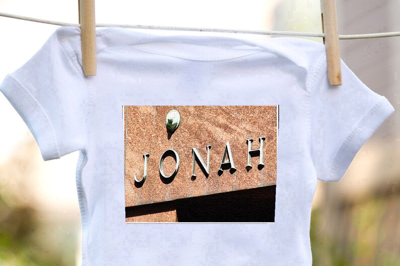 Personalized baby bodysuit featuring the name JONAH showcased in a photo of an actual sign; Baby gift; Baby shower