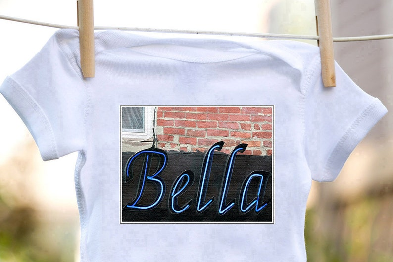 Personalized baby bodysuit featuring the name BELLA showcased in a photo of an actual sign; Baby gift; Baby shower
