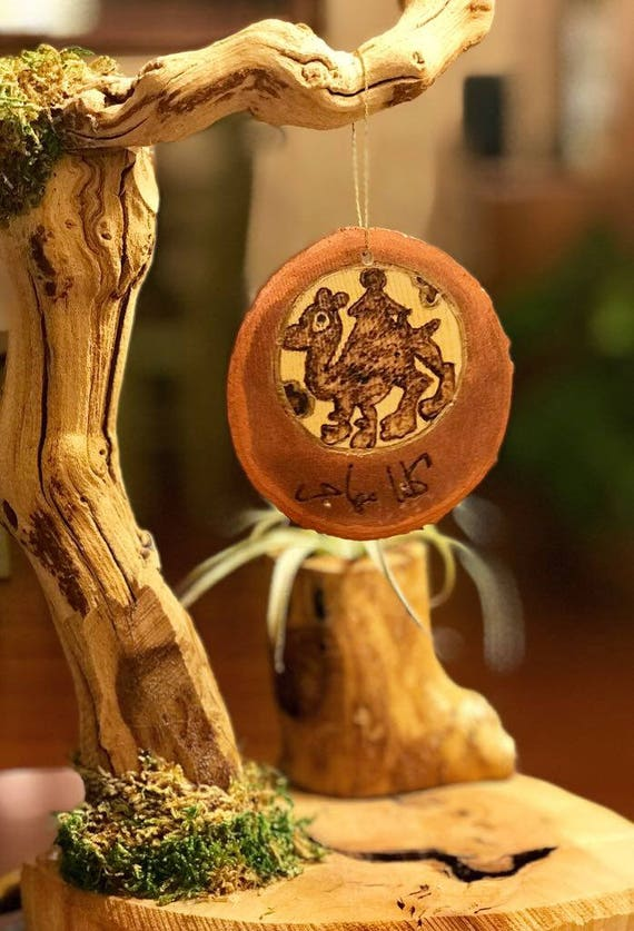 """Handmade Arabic Camel Ornament Which Says, """"We Are All Migrants""""; Christmas ornament; Wood Pendant; tree slice; Arabic calligraphy; camels"""