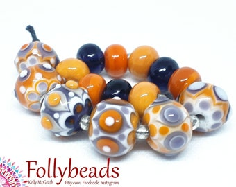 Handmade Lampwork Artisan glass bead set in transparent and opaque Purple, Orange and White.