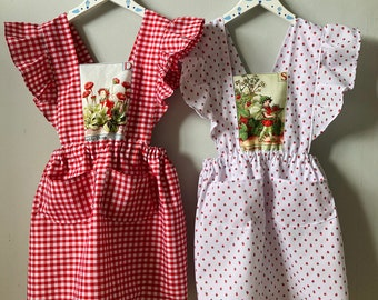 The ROBYN Pinafore Handmade pinafore dress in red floral fabric with cross back straps ruffle hem and pockets